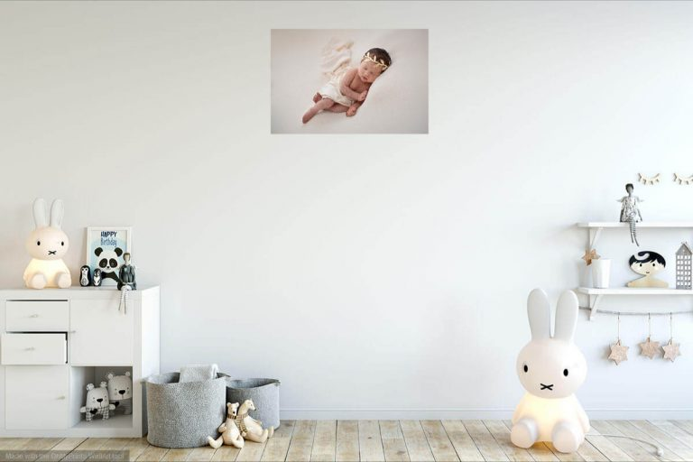 A nursery room with a beautiful canvas showing a newborn baby on the wall
