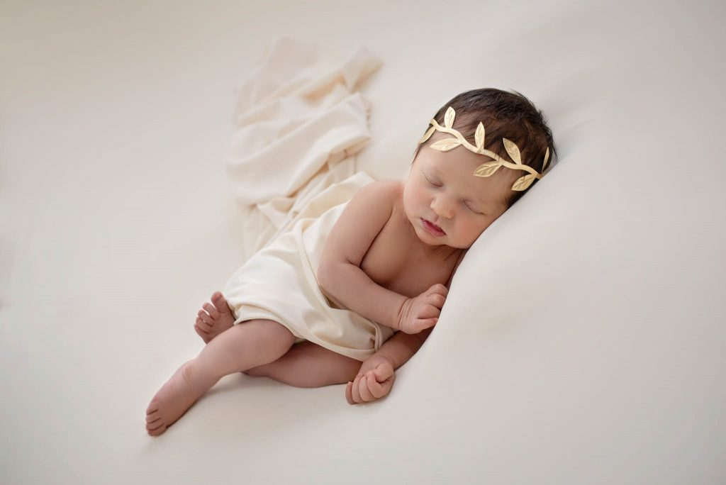 A newborn girl lying on a nude background