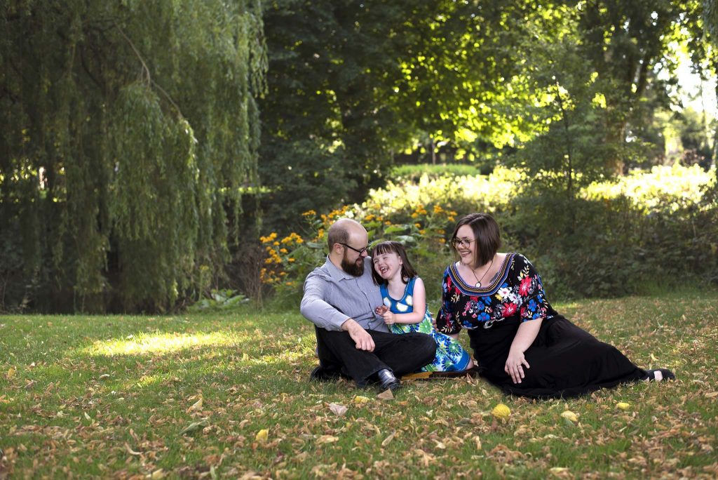 warwickshire photographer taking picture of a family of three sitting on a blanket in a park