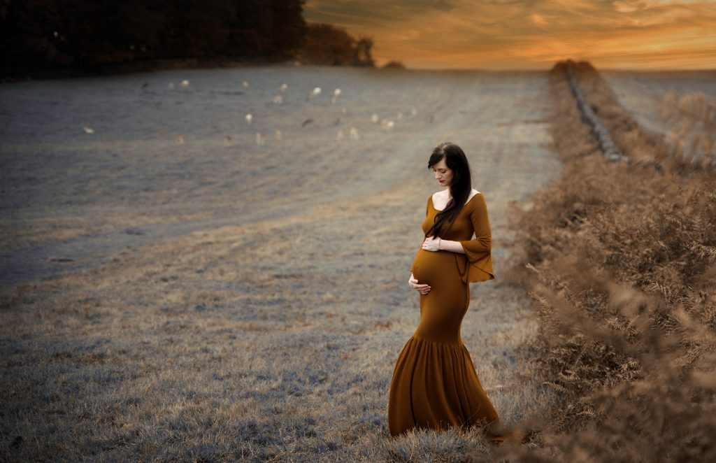 Warwickshire Photographer Monika Mochaupt during her pregnancy having a metrnity photoshoot outside in the fields